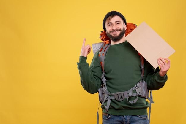 Concetto di viaggio con sorridente ragazzo giovane con packpack e puntando lo spazio libero per scrivere rivolto verso l'alto su giallo