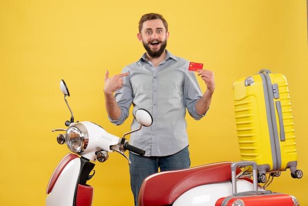 黄色の銀行カードを指すスーツケースを持ってバイクの後ろに立っている笑顔の若い男と旅行のコンセプト