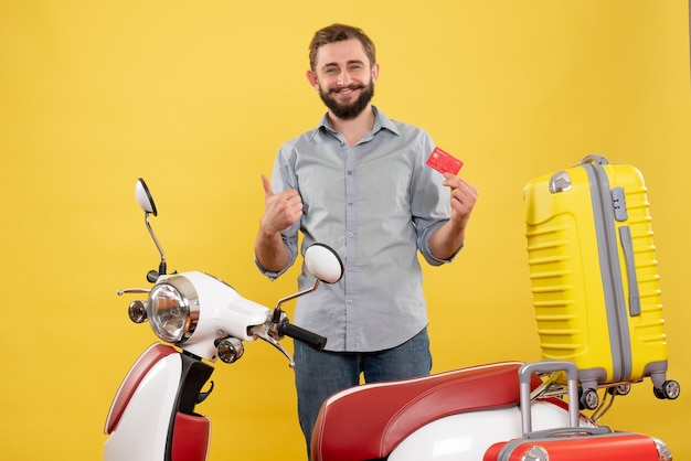 Travel concept with smiling young man standing behind motocycle with suitcases on it and making ok gesture on yellow