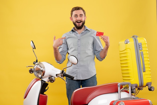 Travel concept with smiling young man standing behind motocycle with suitcases on it pointing bank card on yellow