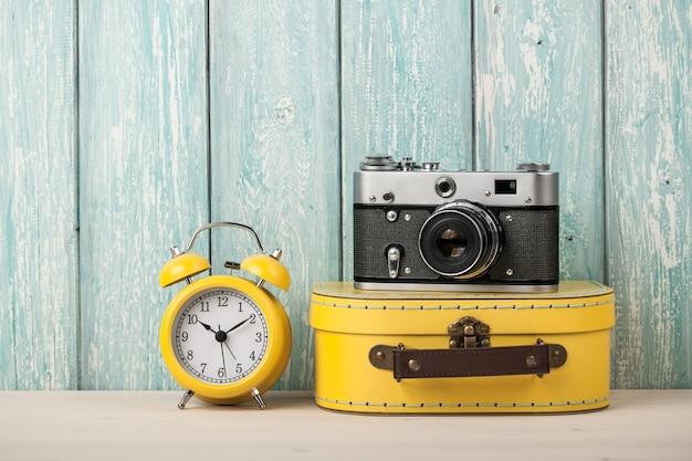 여행 가방, 필름 카메라, 알람 시계가 있는 여행 컨셉
