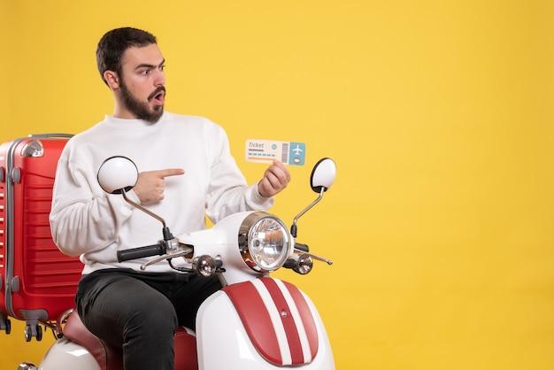 Concetto di viaggio con uomo sorpreso seduto su una moto con la valigia sopra che mostra il biglietto su giallo
