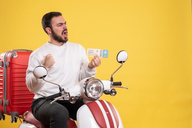 Концепция путешествия с удивленным человеком, сидящим на мотоцикле с чемоданом на нем, показывая билет на желтом