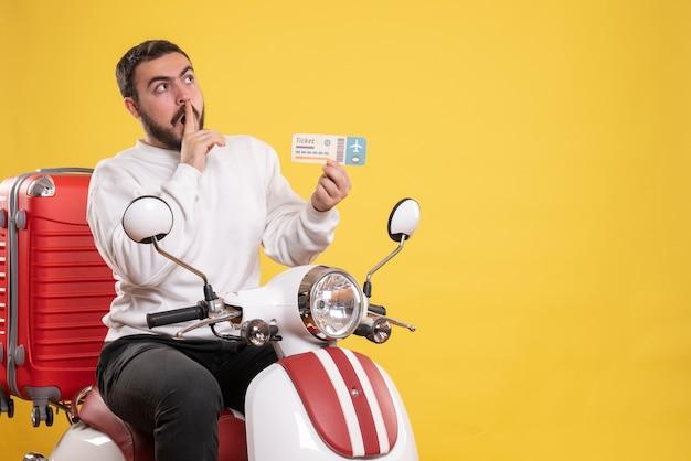 Concetto di viaggio con un uomo in viaggio seduto su una motocicletta con la valigia sopra che mostra il biglietto e alza lo sguardo facendo gesto di silenzio su giallo
