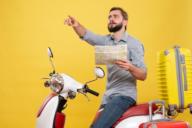 スーツケースを持ってバイクに座って、黄色の地図を保持している不思議な若い男と旅行の概念
