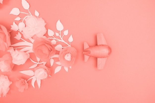Travel concept with wood plane and paper flowers, petals on pink.