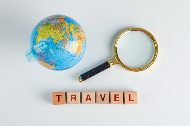 Travel concept with wooden cubes, magnifying glass, globe flat lay.