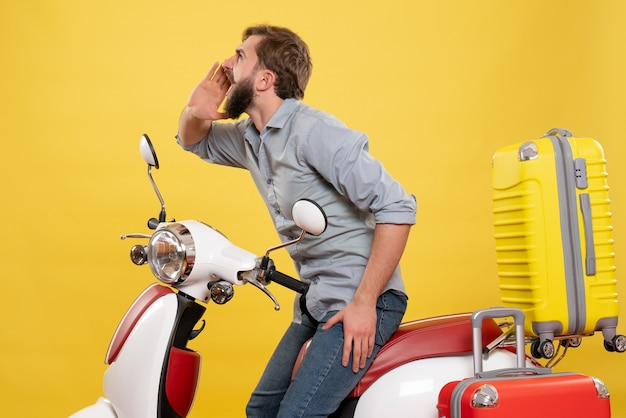Travel concept with young angry and emotional bearded man sitting on motocycle on it calling someone on yellow