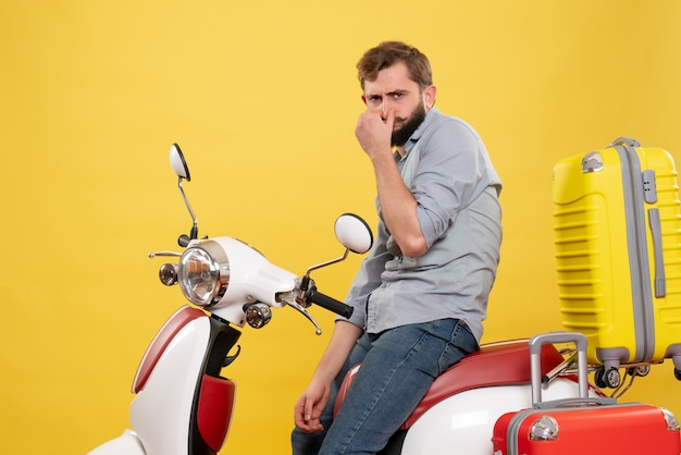 Travel concept with young bearded man sitting on motocycle on it on yellow