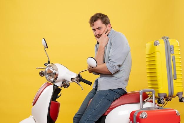 노란색에 그것에 깊은 생각에 motocycle에 앉아 젊은 수염 난된 남자와 여행 개념
