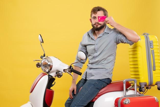 Concetto di viaggio con il giovane barbuto fiducioso uomo seduto sulla moto tenendo la carta di credito su di esso su giallo