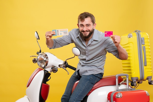 Travel concept with young confident bearded man sitting on motocycle holding bank card and ticket on it on yellow