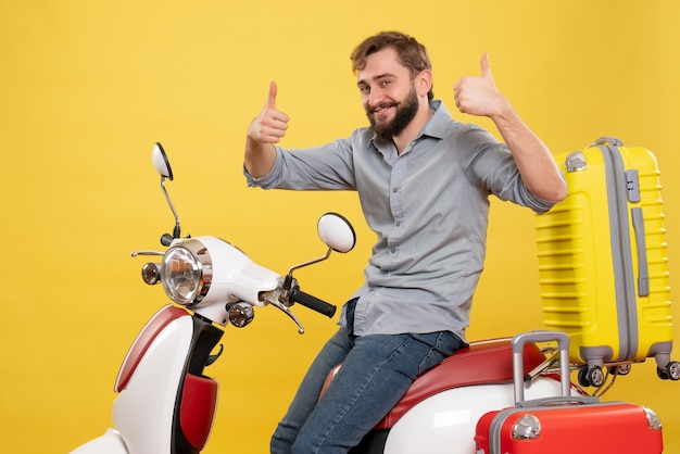 Travel concept with young confident bearded man sitting on motocycle making ok gesture on it on yellow