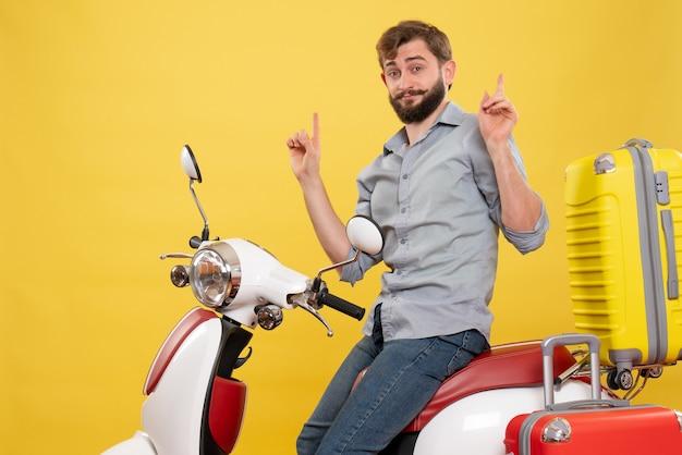 自信を持って若いひげを生やした男性が黄色の上向きにその上にオートバイに座っている旅行の概念