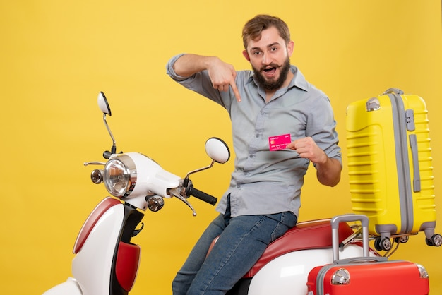 黄色の銀行カードを指しているオートバイに座っている若い自信を持ってひげを生やした男と旅行の概念