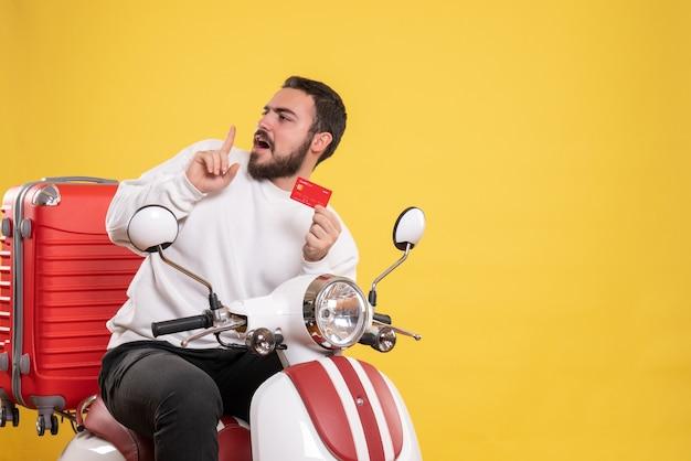 Concetto di viaggio con un giovane uomo in viaggio confuso seduto su una motocicletta con la valigia sopra che mostra la carta bancaria su giallo