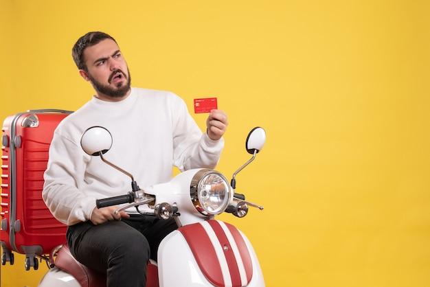 노란색에 은행 카드를 들고 가방에 오토바이에 앉아 젊은 혼란 여행 남자와 여행 개념