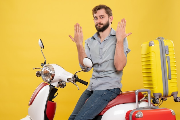 Travel concept with young emotional bearded man sitting on motocycle on it showing hands on yellow