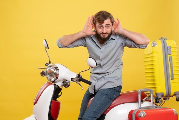 Concetto di viaggio con il giovane uomo barbuto emotivo seduto sulla moto e ascoltando gli ultimi spettegoli su di esso su giallo