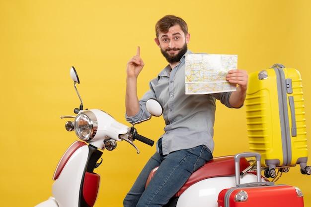 若い感情的なひげを生やした男がバイクに座って、黄色でそれを上向きに地図を持って前方を指している旅行の概念