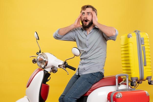 黄色のそれについて深い考えでオートバイに座っている若い感情的なひげを生やした男と旅行の概念