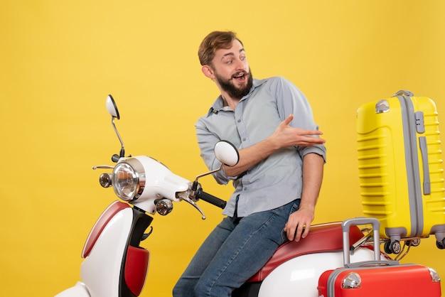 黄色を振り返って、その上にオートバイに座っている若い感情的なひげを生やした男と旅行の概念