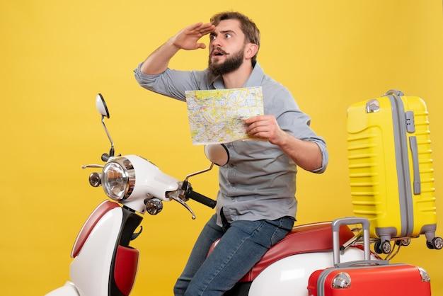 노란색에지도를 보여주는 그것에 motocycle에 앉아 젊은 감정 수염 된 남자와 여행 개념