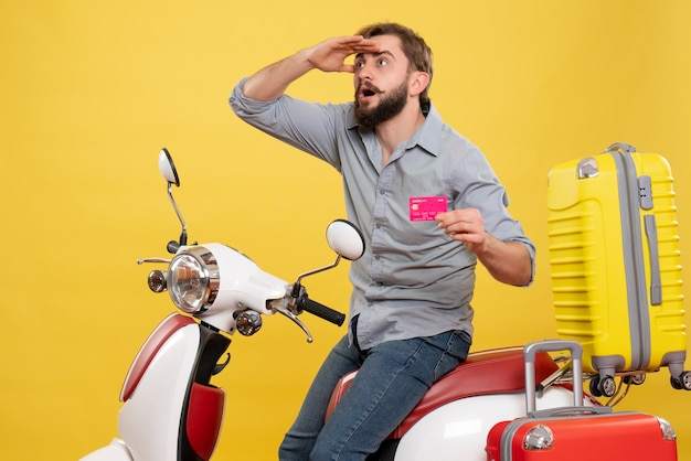 Travel concept with young emotional concentrated bearded man sitting on motocycle and holding bank card on it on yellow