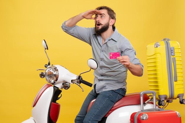 若い感情的な集中ひげを生やした男がオートバイに座って、黄色の銀行カードを保持している旅行の概念