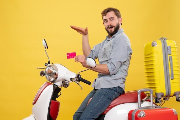 黄色の銀行カードを保持しているその上にオートバイに座っている若い感情的な自信を持ってひげを生やした男と旅行の概念