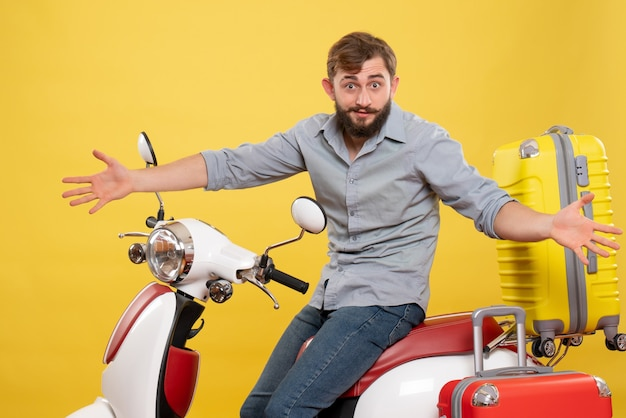 Travel concept with young emotional curious bearded man sitting on motocycle on it on yellow