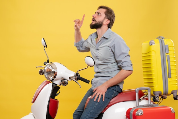 Travel concept with young focused bearded man sitting on motocycle and looking up on it on yellow