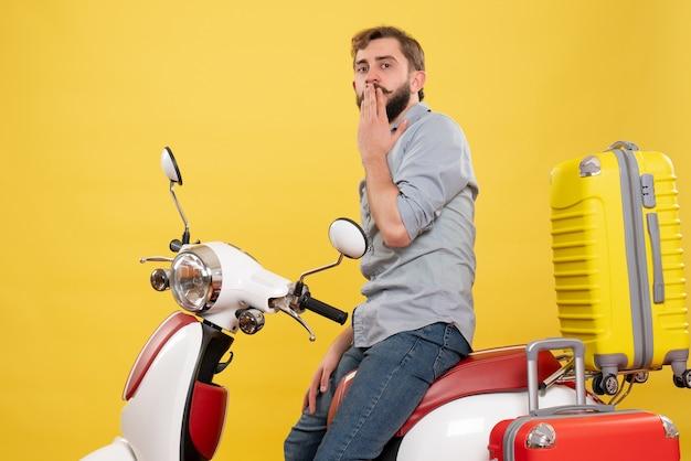 黄色に乗ってバイクに座っている若い焦点を当てたひげを生やした男と旅行の概念