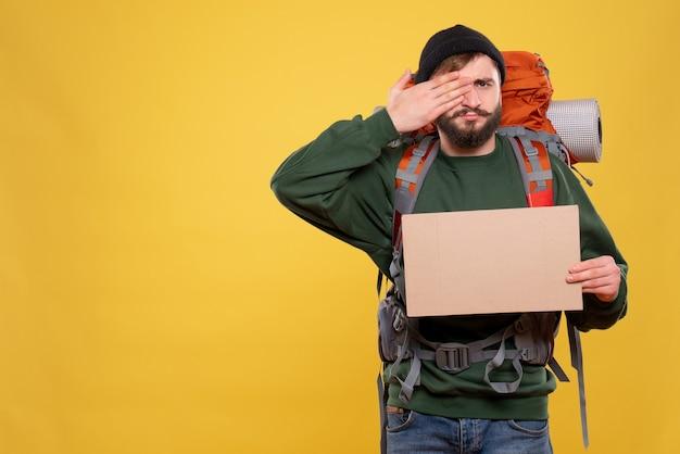 パックパックと書くための空きスペースを指す若い男との旅行の概念は、黄色の彼の目の片方に手を置きます