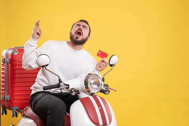 Travel concept with young hopeful emotional travelling man sitting on motorcycle with suitcase on it holding bank card on yellow
