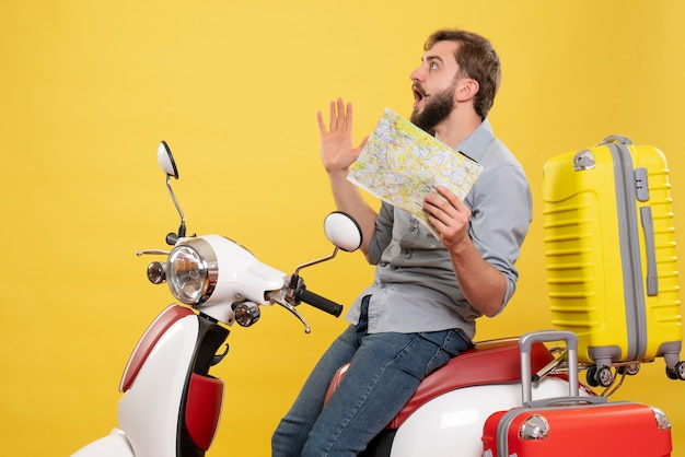Travel concept with young nervous bearded man sitting on motocycle and showing map on it on yellow