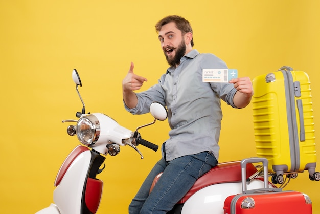Travel concept with young smiling bearded man sitting on motocycle and pointing ticket on it on yellow