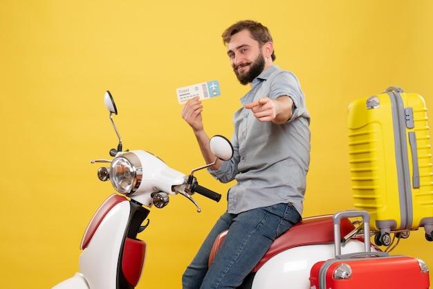 若い笑顔のひげを生やした男がオートバイに座って、黄色のチケットを持って前方を指している旅行の概念