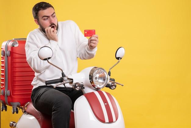노란색에 은행 카드를 들고 가방에 오토바이에 앉아 젊은 놀된 여행 남자와 여행 개념