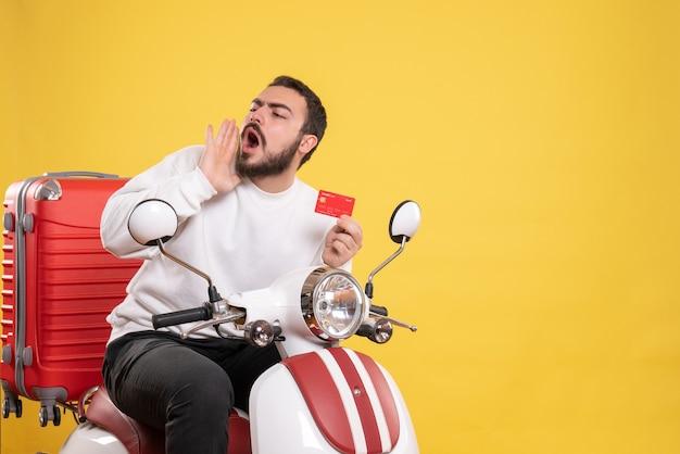 Concetto di viaggio con un giovane uomo in viaggio seduto su una moto con la valigia sopra che tiene una carta bancaria che chiama qualcuno in giallo