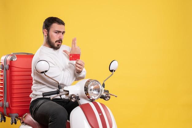 Concetto di viaggio con un giovane uomo in viaggio seduto su una moto con la valigia sopra che tiene la carta di credito che fa il gesto della pistola sul giallo on