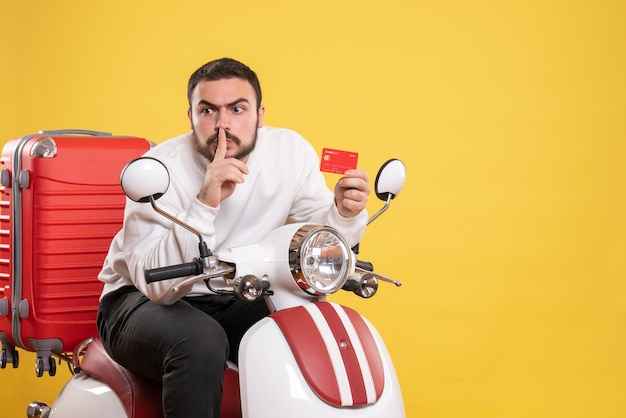 Concetto di viaggio con un giovane uomo in viaggio seduto su una moto con la valigia sopra che tiene in mano una carta bancaria che fa un gesto di silenzio su giallo
