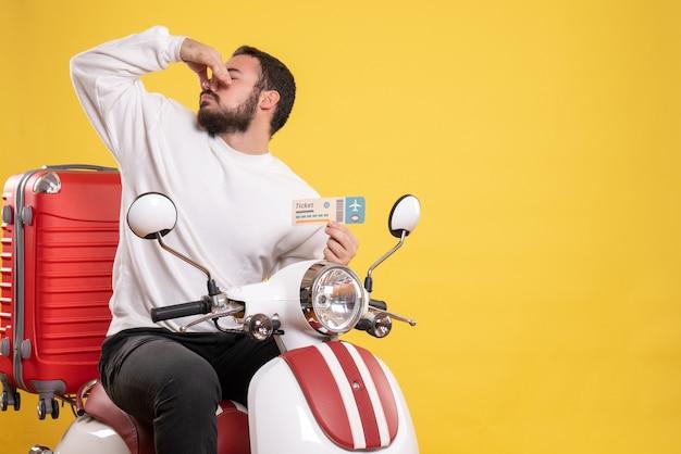 은행 카드를 보여주는 그것에 가방으로 오토바이에 앉아 젊은 여행 남자와 여행 컨셉