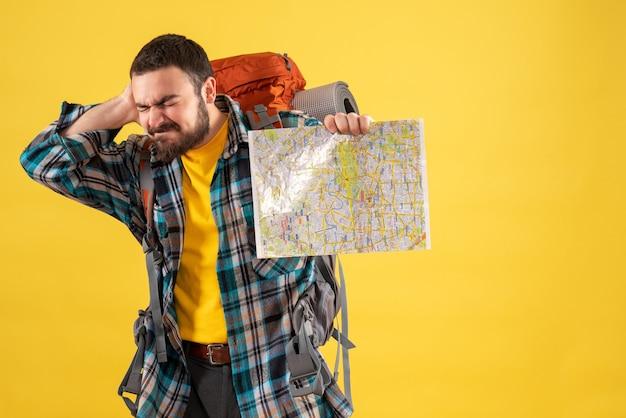 Concetto di viaggio con un giovane ragazzo in viaggio problematico con uno zaino che tiene in mano una mappa che soffre di dolore al collo su giallo