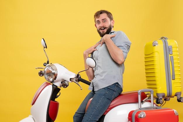 若い不思議なひげを生やした男がオートバイに座って、黄色でそれに自分自身を指していると旅行の概念