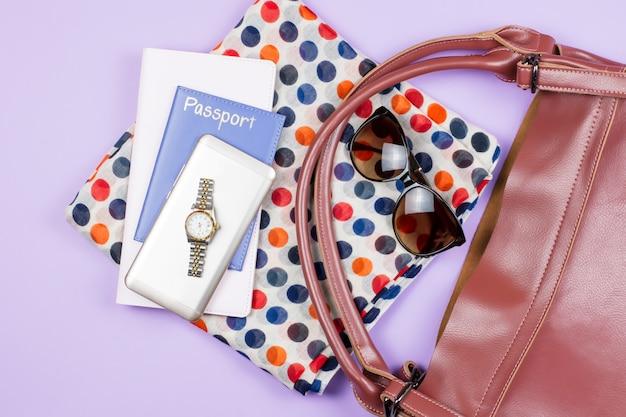 旅行の概念-女性ファッションアクセサリー、腕時計、斑点のあるスカーフ、サングラス、パスポート、メモ帳、スマートフォン