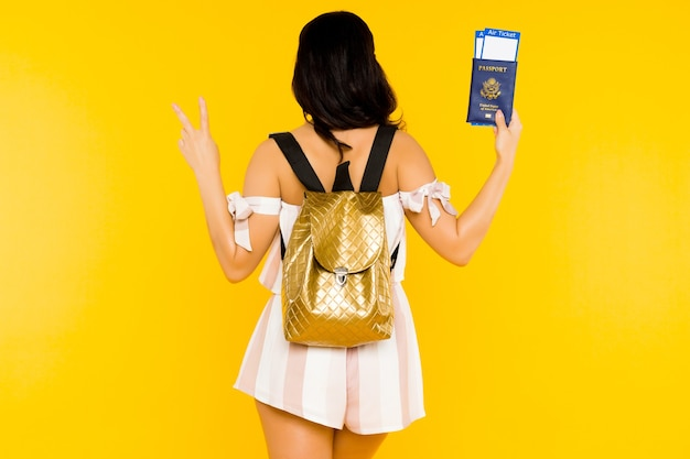 Travel concept. young asian woman holding passport with tickets standing back with knapsack shows peace sign on yellow space