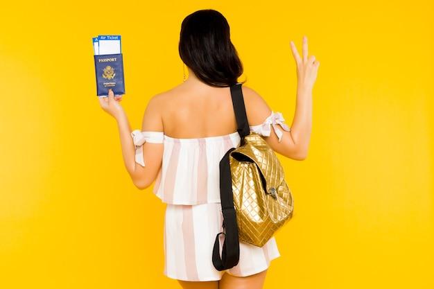 Концепция путешествия. молодая азиатская женщина, держащая паспорт с билетами, стоящими назад