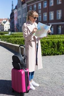 여행 개념 - 도시에서 여행가방을 잃어버린 젊고 아름다운 여성 여행자