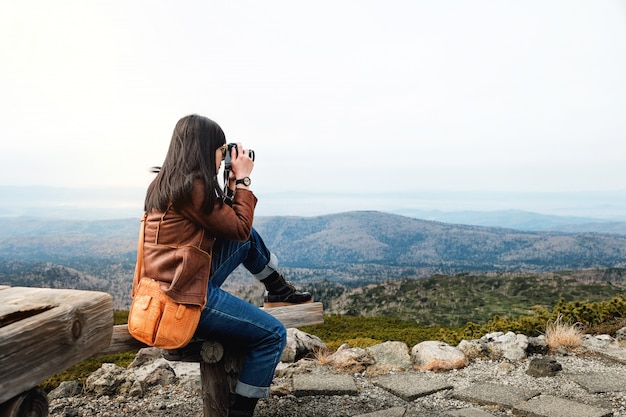 Travel concept. young traveling woman with camera taking photo in fall